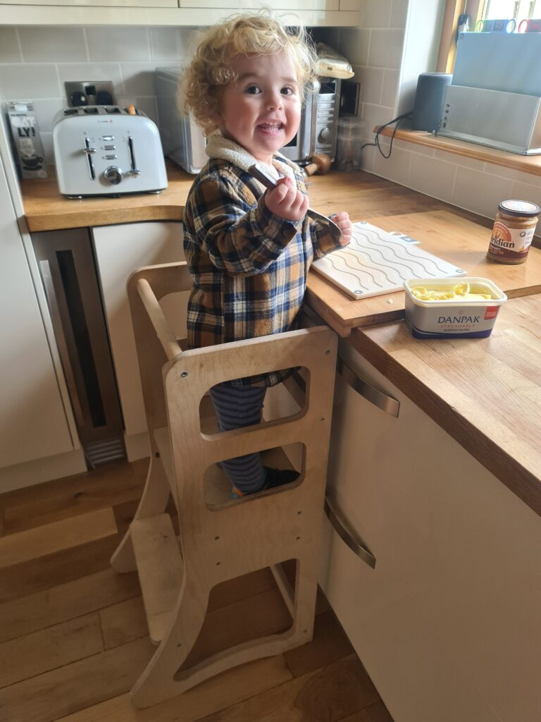 Child buttering toast, using learning tower